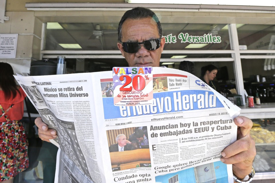 "Francisco Gil reads the announcement of the reopening of embassies in Havana and Washington, Wednesday, July 1, 2015, in the Little Havana area of Miami. President Barack Obama announced Wednesday that the U.S. and Cuba will reopen their embassies in Havana and Washington, heralding a ""new chapter"" in relations after a half-century of hostility. (AP Photo/Alan Diaz)"